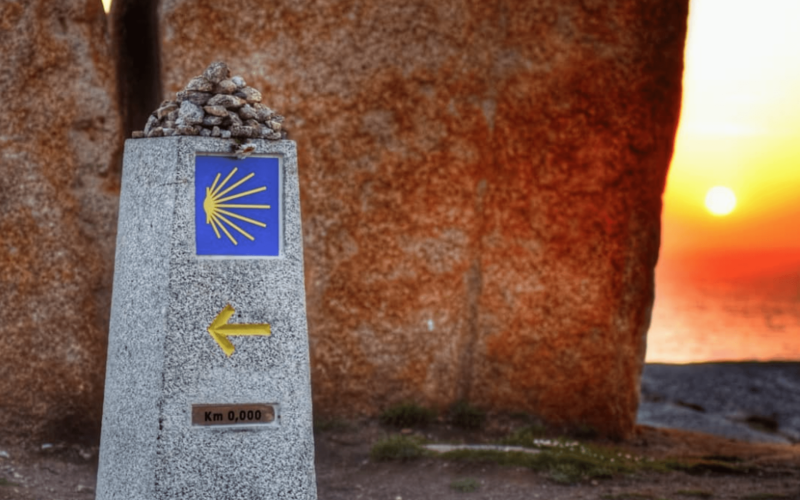 Camino Marker at Zero Km with sunset in the background