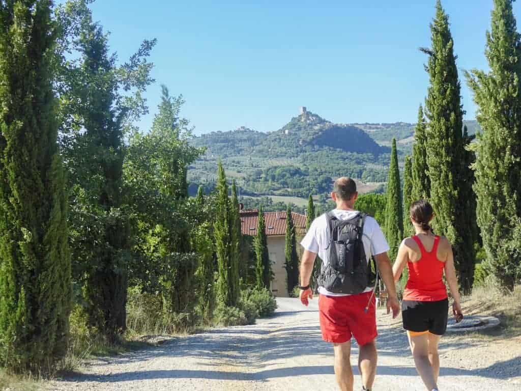 Via Francigana - Couple in walking gear walking on the stone path