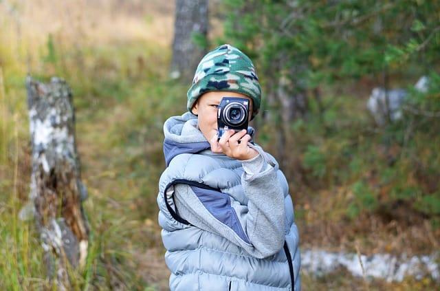 child taking photo on holiday