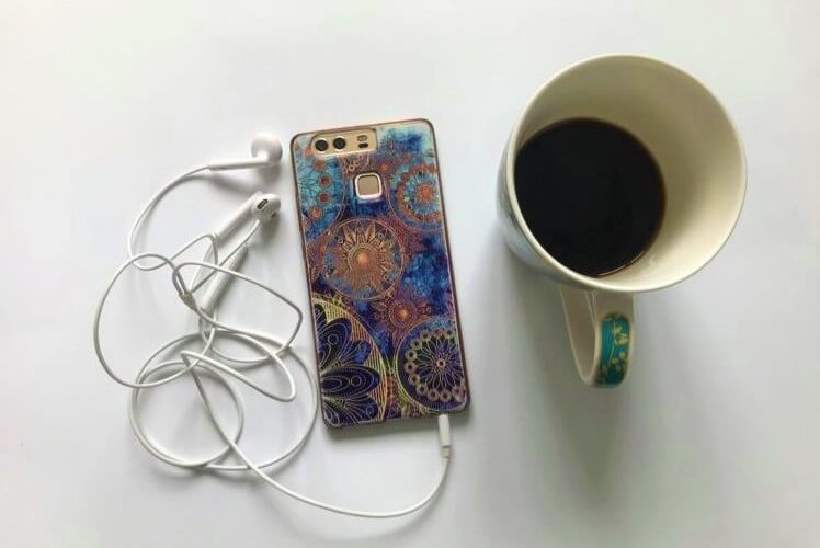 phone playing podcast with headphones and coffee