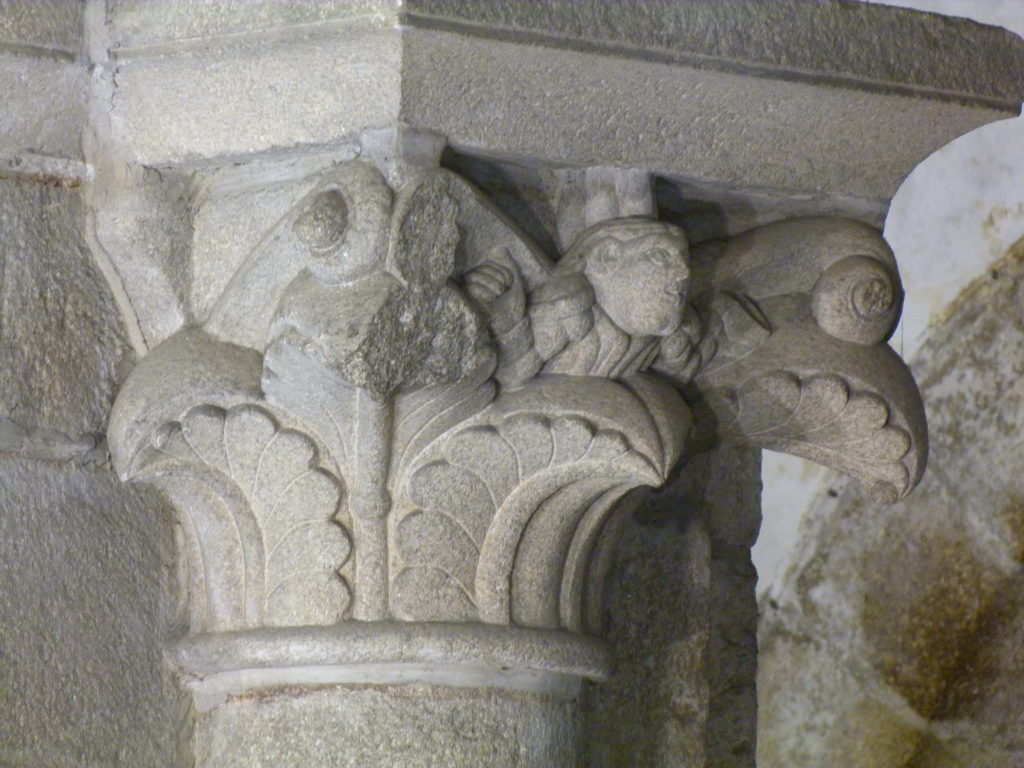 a smiling face of a stonemason in the capital of a column in the cathedral