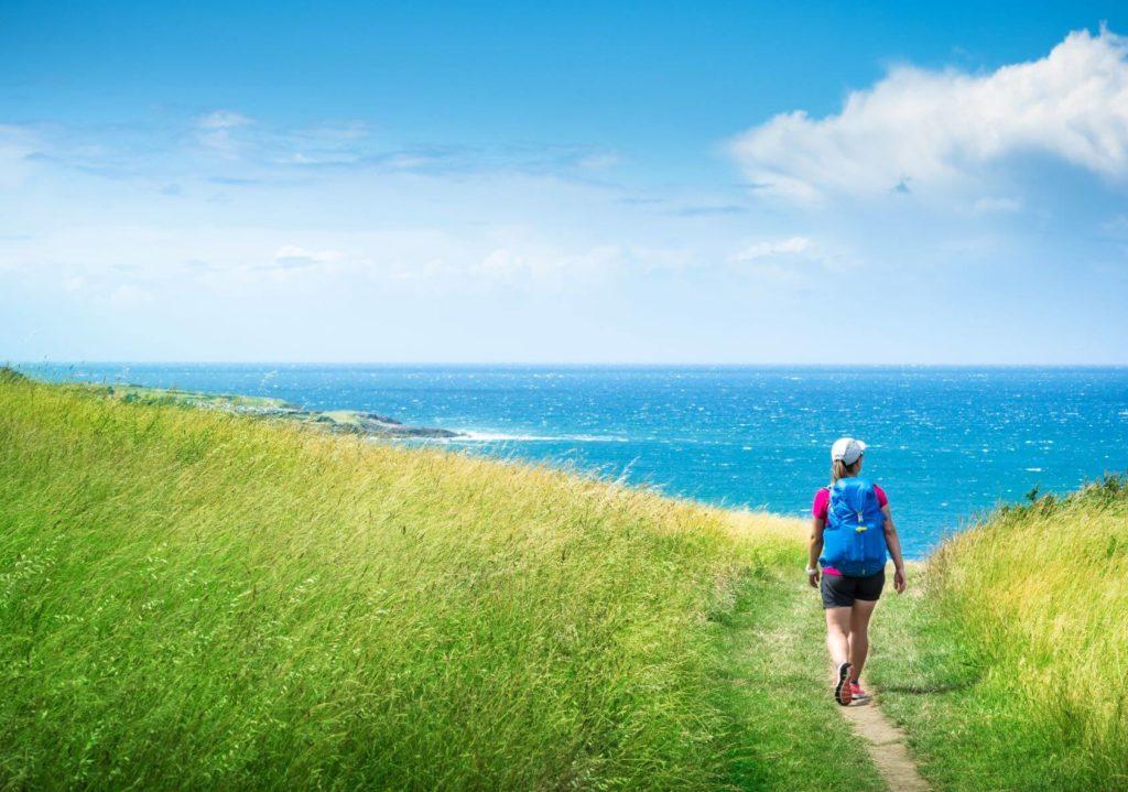 woman walks on the camino del norte towards the sea