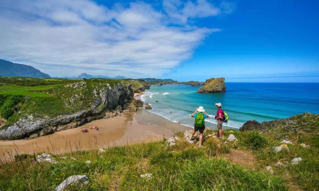 pilgrims on the camino del norte looking at san martin beach