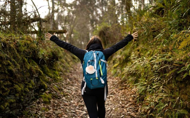 happy pilgrim young woman on the train path road walking backpack
